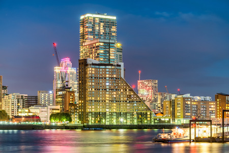 Amazing night skyline of Canary Wharf with river reflections, London.