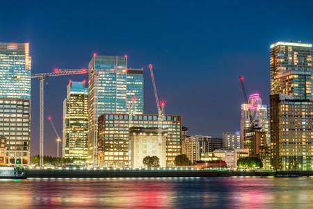 wharf: Canary Wharf modern buildings night reflections.