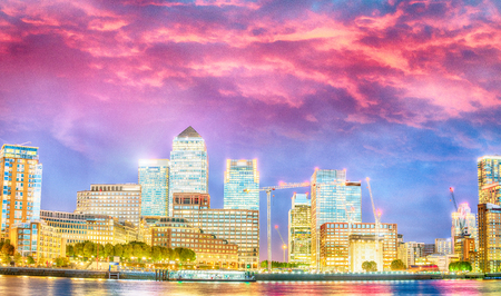 Canary Wharf skyscrapers. Panoramic sunset view with water reflections - London - UK Stock Photo