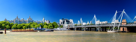 annually: LONDON - JUNE 30, 2015: Panoramic view of Hungerford Bridge on a beautiful summer day. London attracts 30 million people annually.