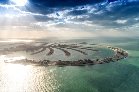Stunning aerial view of Palm Jumeirah at sunset with sun rays on the ocean - Dubai.