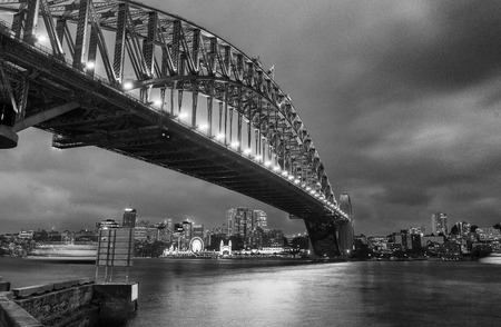 Black and white wide angle view of Sydney Harbour Bridge at night.