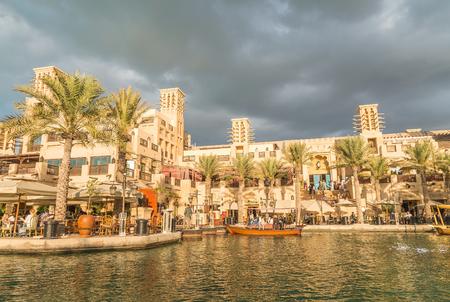 DUBAI - DECEMBER 11, 2016: Madinat Jumeirah buildings with tourists. Dubai attracts 15 million people annually.