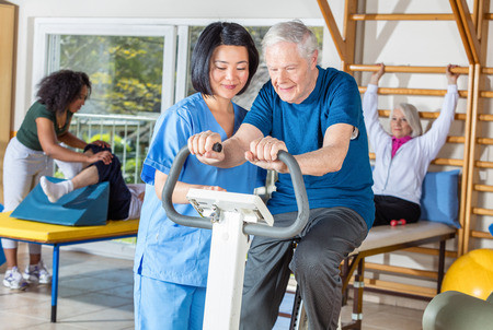 Asian nurse helping elder man in hospital gym.