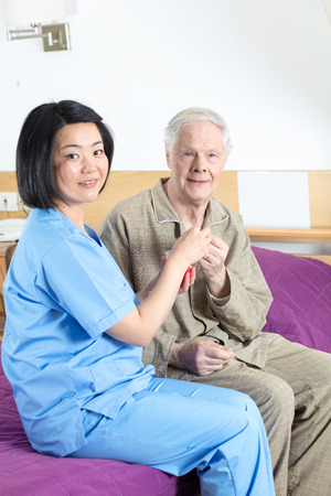 doctor giving glass: Asian nurse handing glass of water and pill to elderly man in hospital.