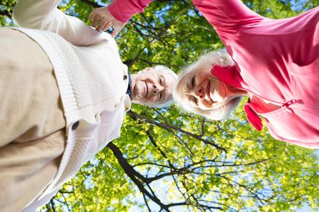 Upward view of happy elderly couple in the garden.