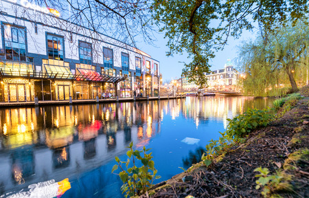 princes street: AMSTERDAM - MAY 1, 2013: City canals at night for Queens Day. Amsterdam attracts 10 million visitors every year. Editorial
