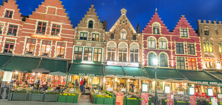 BRUGES, BELGIUM - MARCH 2015: Tourists visit ancient medieval city at night. Brugge attracts more than 2 million people annually. Editorial