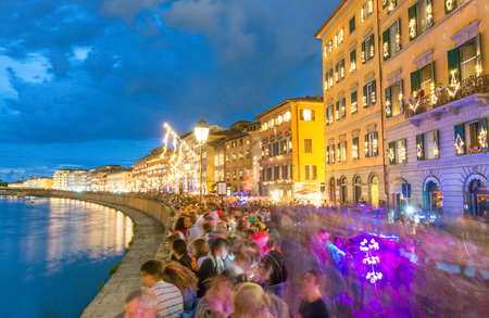 PISA - JUNE 16, 2015: Tourists and locals at night enjoy famous Luminara. This is a light show throughout the whole city. Editorial