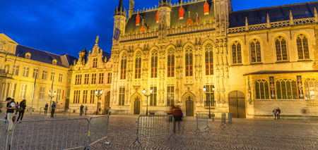 BRUGES, BELGIUM - MARCH 2015: Tourists visit ancient medieval Burg Square at night. Brugge attracts more than 2 million people annually. Editorial