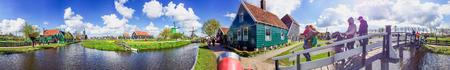 ZAANSE SCHANS, NETHERLANDS - APRIL 2015: Tourists visit windmills. This is a famous tourist attraction.