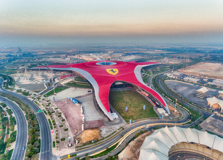 ABU DHABI, UAE - DECEMBER 6, 2016: Ferrari World Park is the largest indoor amusement park in the world. The roof has a total surface area of 200,000 sqm. Imagens - 75699118
