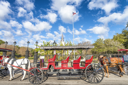 NEW ORLEANS, USA - FEBRUARY 2016: Red horse carriage along Jackson Square. New Orleans attracts 10 million tourists annually. Editorial