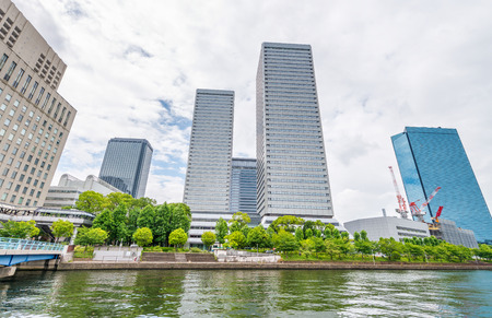 water bus: Osaka skyline along city river.