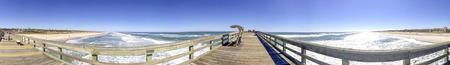 Tourists walk along St Johns County Ocean Pier in St Augustine, FL.