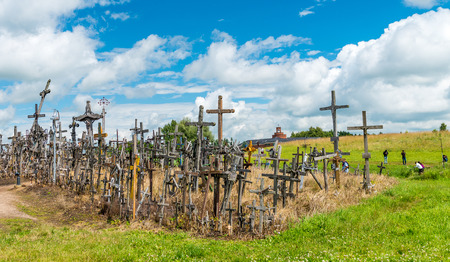 SIAULIAI, LITHUANIA - JULY 9, 2017: Tourists and pilgrims visit Hill of Crosses. The Hill Of Crosses in northern Lithuania has been a site of pilgrimage for hundreds of years.