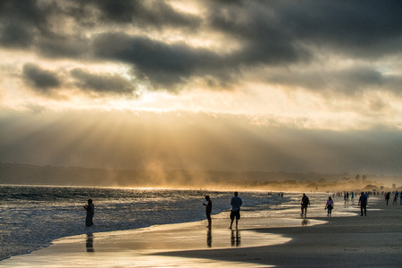 Backlit people on the beach at sunset, San Diego. Éditoriale