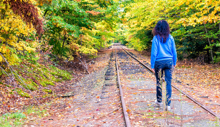 Woman walking in foliage environment.