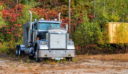 Powerful truck surrounded by foliage trees, New England.