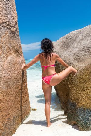 Back view of beautiful woman relaxing on La Digue rocks, Seychelles. 版權商用圖片