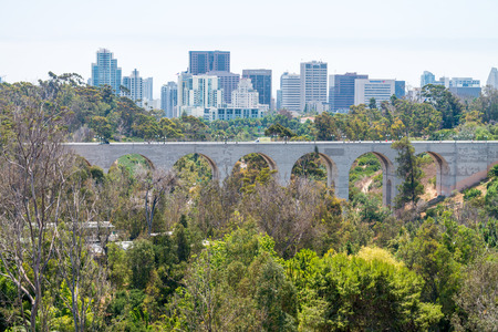 SAN DIEGO - JULY 30, 2017: Bridge and San Diego skyline with trees on foreground.
