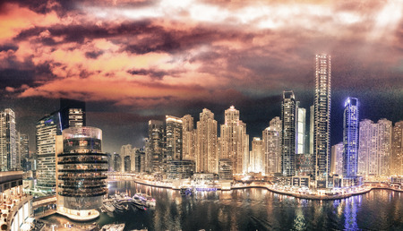 Dubai Marina night aerial skyline from rooftop. Beautiful skyscrapers over artificial canal.
