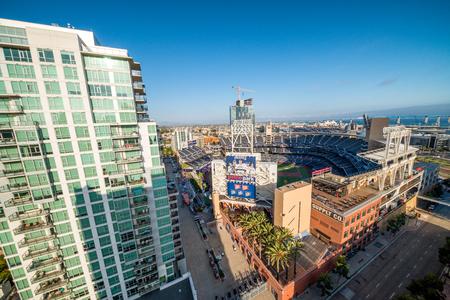 ballpark: SAN DIEGO - JULY 29, 2017: Petco Park and Coronado Bridge on background. San Diego attracts 20 million people annually.