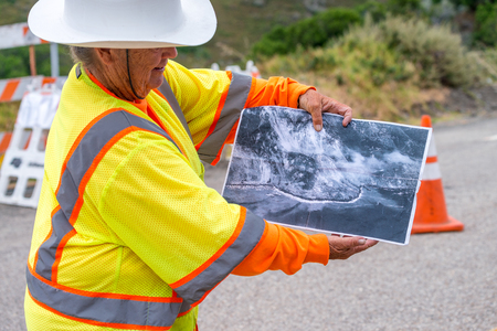BIG SUR, CA - AUGUST 3, 2017: Woman shows winter landslide damage in Cabrillo Highway. The road is still under construction. Editorial