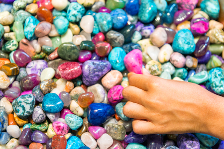 Child hand touching colourful stones. Banque d'images