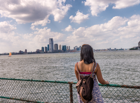 Woman looking at Jersey City skyline from New York.