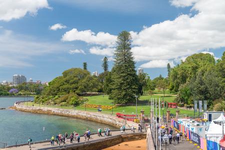 SYDNEY - OCTOBER 2015: Tourists walk along Royal Botanic Garden. Sydney attracts 15 million people annually.