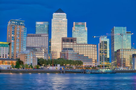 Canary Wharf buildings at night with river reflections.