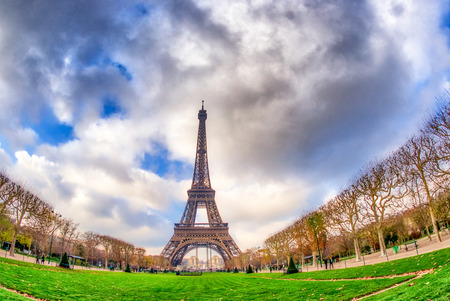 Wide angle upward view of Tour Eiffel as seen from surrounding gardens.