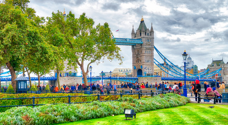 LONDON - SEPTEMBER 25, 2016: Tourists visit the Tower Bridge. London attracts 30 million people annually.