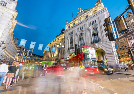 LONDON - JUNE 2015: Red buses and tourists along Regent Street at night. London attracts 30 million visitors annually. Editorial