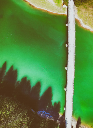 Bridge crossing beautiful mountain lake, overhead panoramic aerial view.