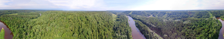 Panoramic aerial view of forest and river at dusk.