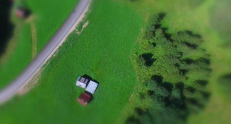 Road across mountain meadow, overhead aerial view. Stock Photo
