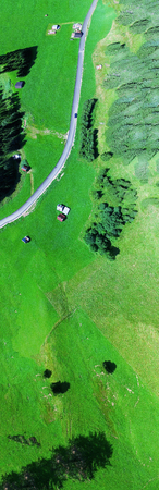 Road across mountain meadows, overhead panoramic aerial view.