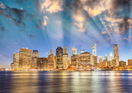 Downtown Manhattan sunset light with river reflections from Brooklyn, New York City. Editorial
