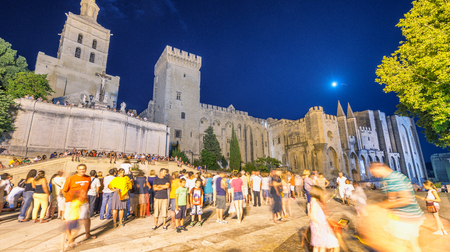 AVIGNON, FRANCE - JULY 20, 2014: Torists in main square at night. Avignon is one of the most famous cities in France.