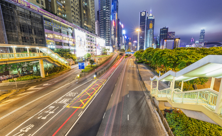 HONG KONG - APRIL 2014: City skyscrapers and roads with cal light trails at night. Hong Kong attracts 25 million people annually.