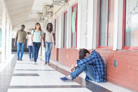 School bullying. Caucasian male teenager desperate seated in school hallway while group of teenagers walk towards him. Stockfoto
