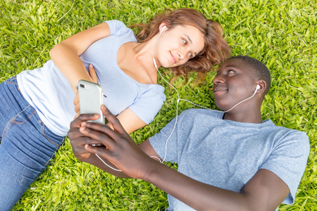 African boy and caucasian girl laying on the grass hearing music. Stock Photo
