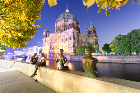 Beautiful night view of Berlin Cathedral and statues along Spree river.