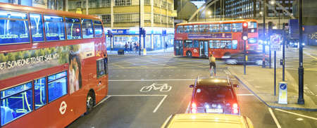 LONDON - JULY 2, 2015: Red buses along city streets. They are a major city attraction for tourists.