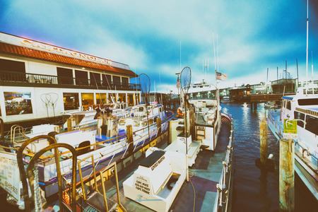 SAN FRANCISCO - AUGUST 7, 2017: Boats docked in Fishermans Wharf at night. The city attracts 20 million tourists annually. Editorial