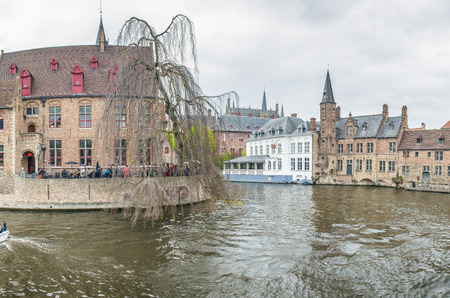 BRUGES, BELGIUM - MARCH 2015: Tourists visit ancient medieval city on a cloudy day. Brugge attracts more than 2 million people annually.