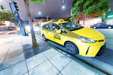 SAN DIEGO, CA - JULY 30, 2017: Taxi Cab in Little Italy at night. This is a street full of restaurants and shops.