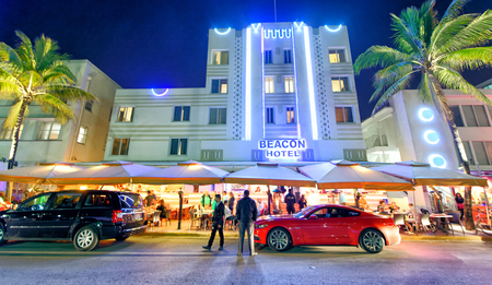 MIAMI BEACH - FEBRUARY 25, 2016: Tourists enjoy night time in Ocean Drive. The city attracts 25 million visitors every year.